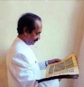 (Dr. Naram studying the ancient manuscripts)
